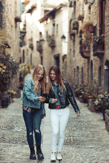 Young women walking and photographing in quaint village