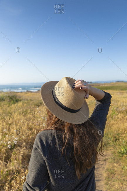 A stylish woman in her twenties wearing a hat and enjoying sunset along California coastline on a warm spring day