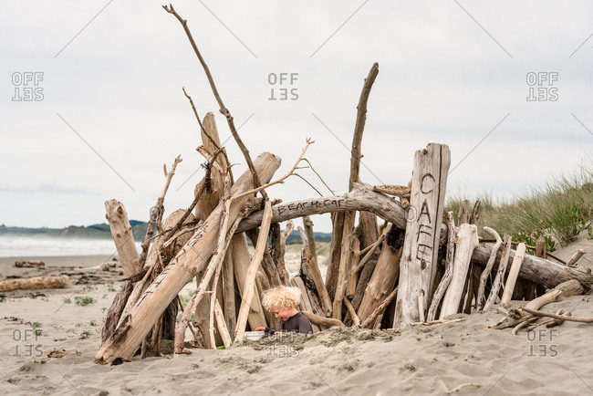 Young boy playing in fort on beach