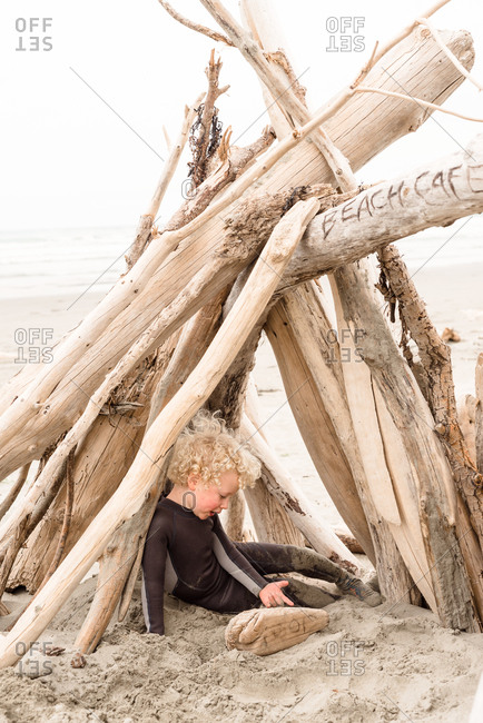 Young boy playing in driftwood fort on beach