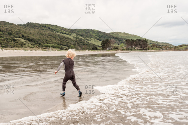 Boy running from waves on Hawke's Bay, New Zealand