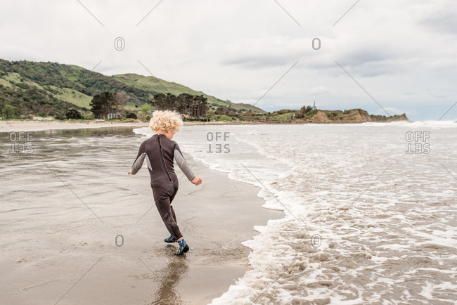 Boy running from waves on the coast of Hawke's Bay, New Zealand
