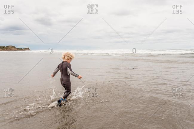 Boy splashing in waves on Hawke's Bay, New Zealand