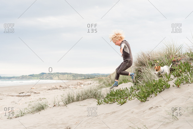 Boy running on sandy hill with dog