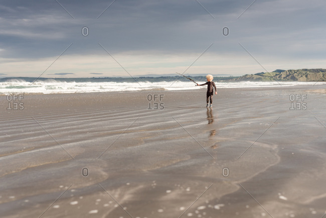 Boy with stick in the tide on Hawke's Bay, New Zealand