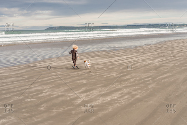 Boy running with dog on beach