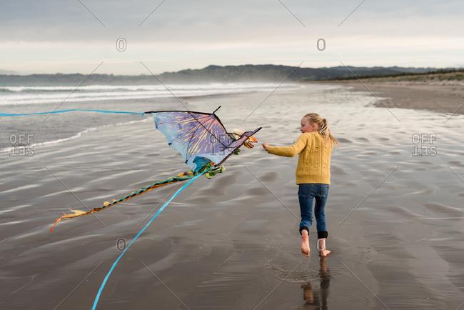 Girl flying kite on the coast of Hawke's Bay, New Zealand