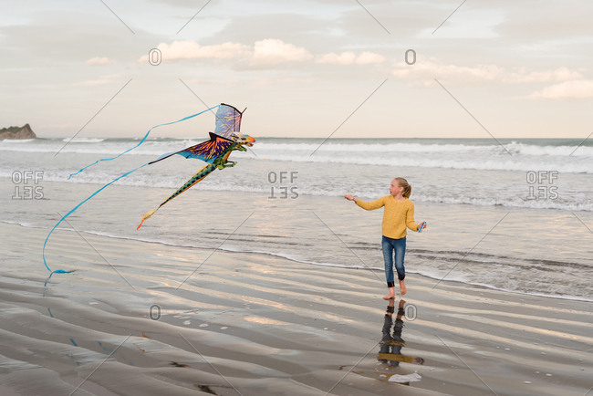 Girl flying dragon kite on the beach, Hawke's Bay, New Zealand