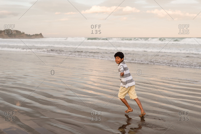 Boy running with sparklers on beach at sunset