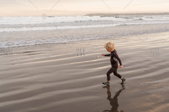 Boy with sparklers on beach at sunset