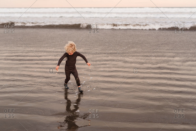 Boy playing with sparklers on beach at sunset