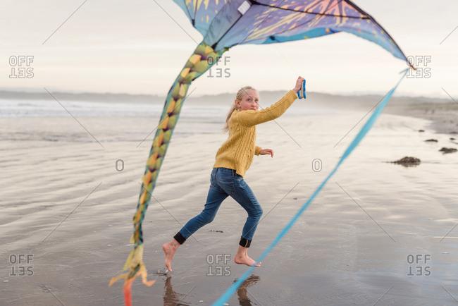 Girl flying a kite on the beach, Hawke's Bay, New Zealand