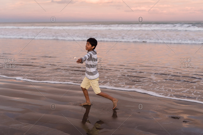 Young boy running with sparklers on beach at sunset