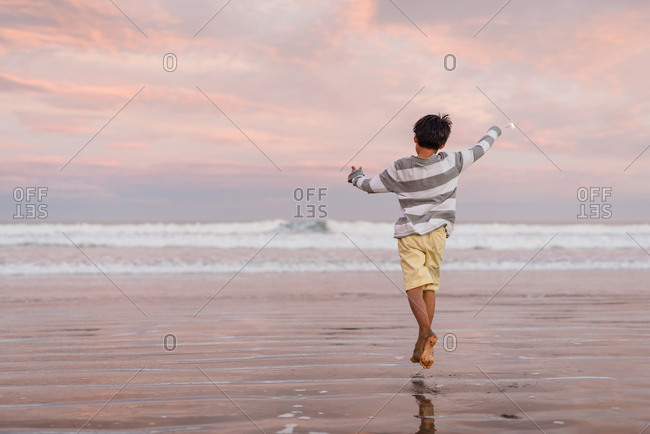Rear view of boy running with sparklers on beach at sunset