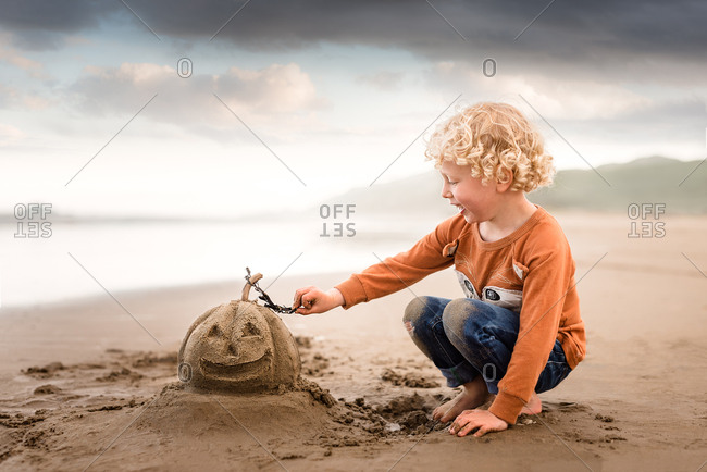 Boy building sand pumpkin on a beach