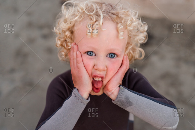 Portrait of boy with blonde curly hair making silly face