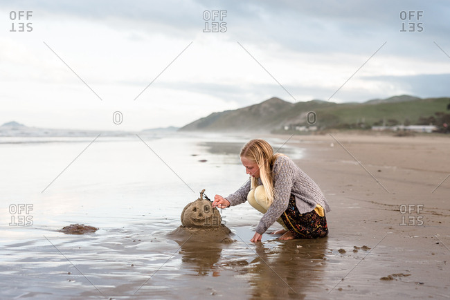 Girl building a jack-o-lantern out of sand