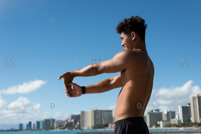 Young man exercising near seaside on a sunny day