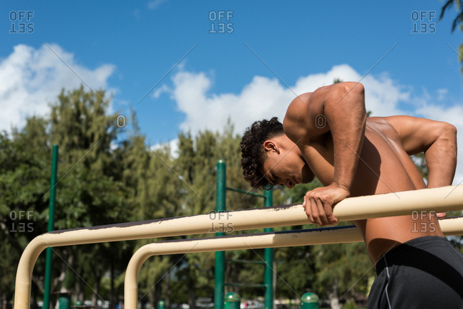 Man exercising on parallel bar in the park on a sunny day