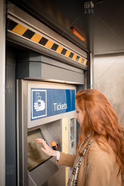 Woman using automatic vending machine at railway station