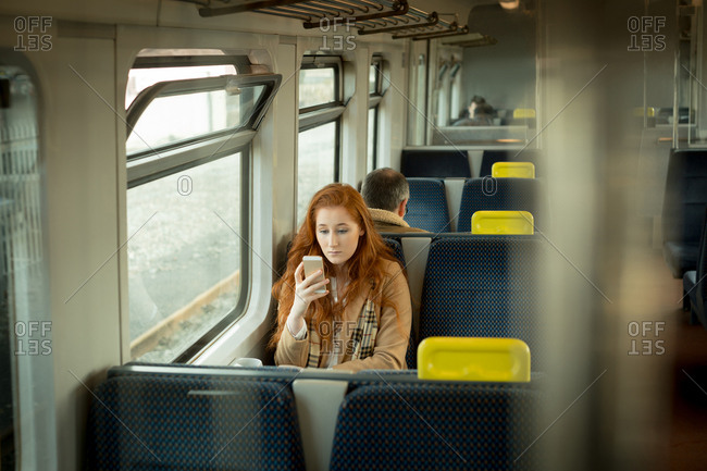 Beautiful woman using mobile phone while travelling in train