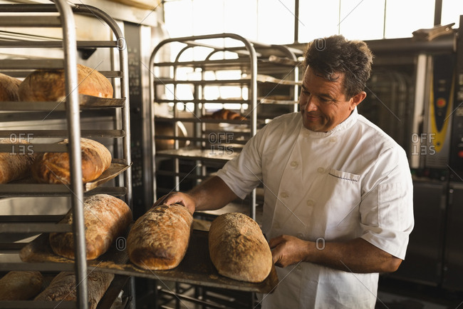 Male baker checking baked bread in bakery shop
