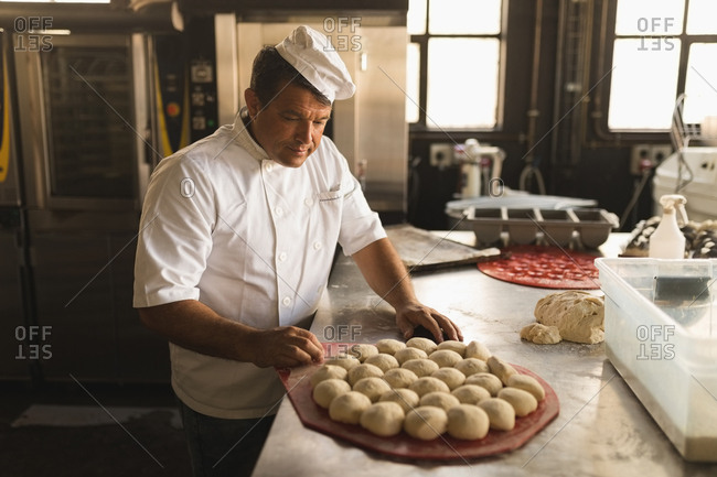 Mature male baker with dough balls in bakery shop
