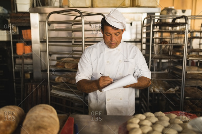 Male baker writing on a notepad in bakery shop