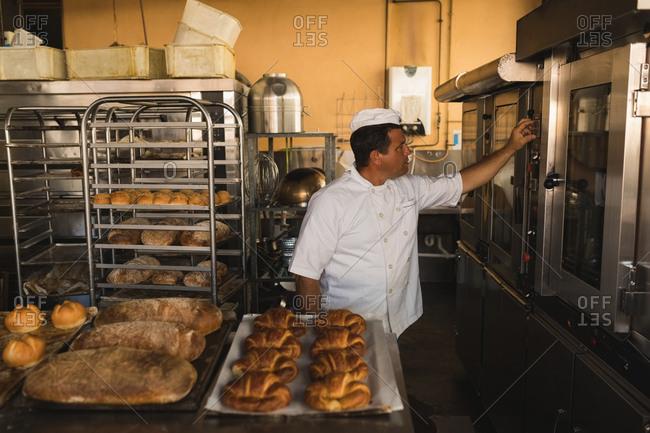 Mature male baker working in baker shop