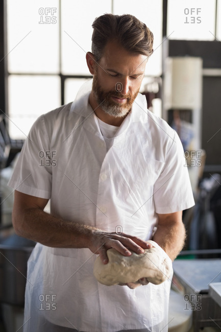 Mature male baker holding a dough in bakery shop