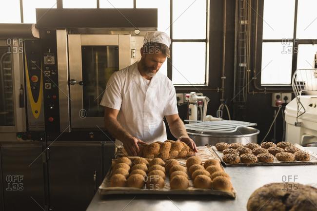 Male baker arranging baked sweet foods in bakery shop
