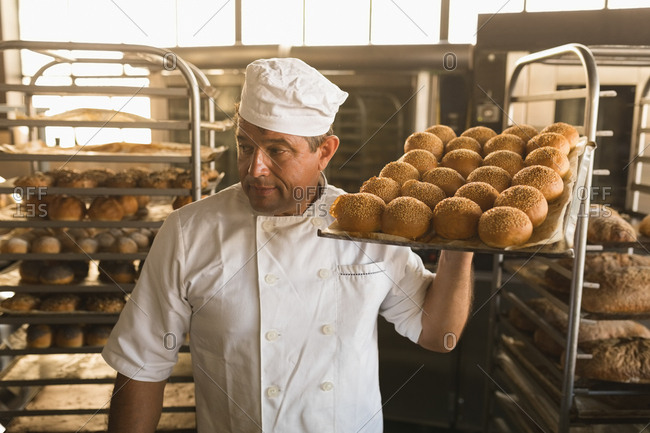Male baker holding a tray of baked sweet foods in bakery shop