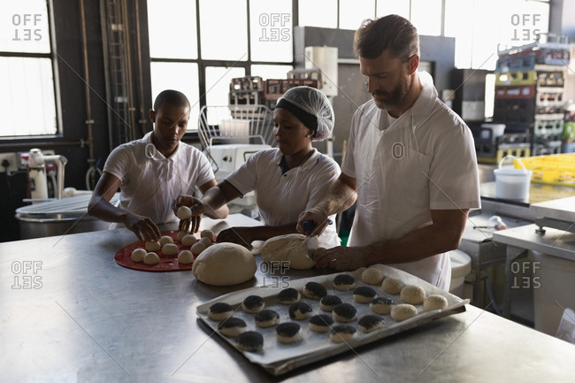 Male baker with coworkers preparing dough in bakery shop