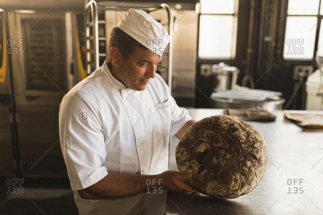 Male baker examining a dough in bakery shop