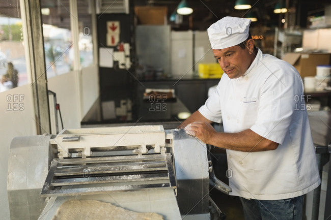 Mature male baker using machine in bakery shop