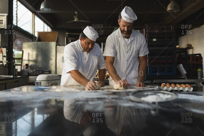 Male baker preparing dough with his coworker in bakery shop