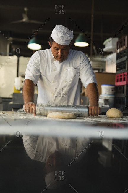 Mature male baker using rolling pin in bakery shop