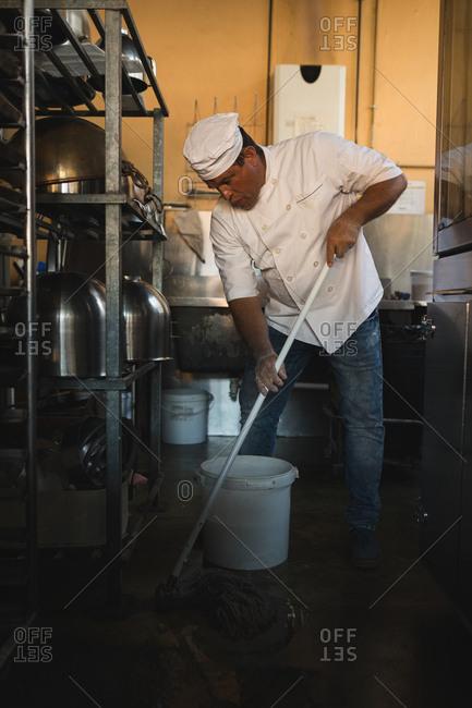 Male baker cleaning floor with floor mop in bakery shop