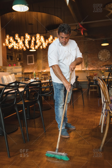 Male baker cleaning floor with floor mop in cafe