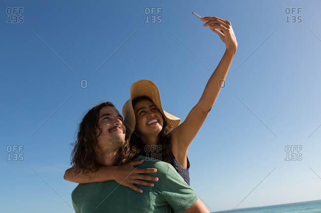 Couple taking selfie with mobile phone in the beach