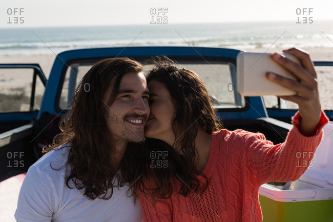 Couple taking selfie with mobile phone in a pickup truck at beach