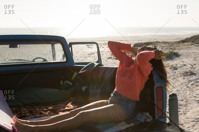 Woman relaxing in a pickup truck at beach