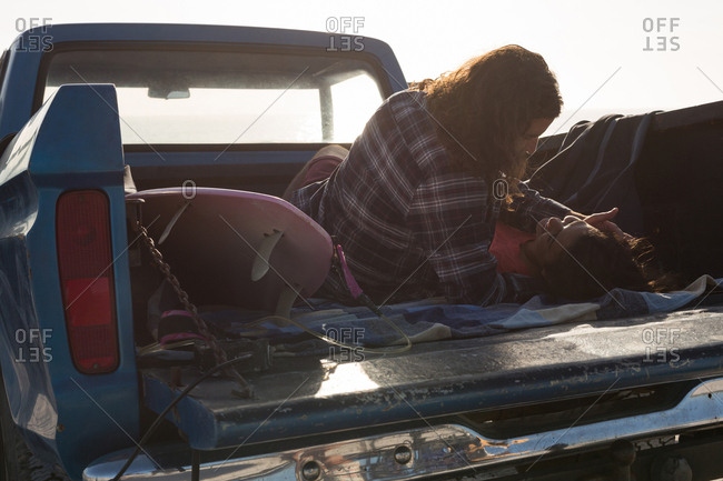 Couple romancing in a pickup truck at beach on a sunny day