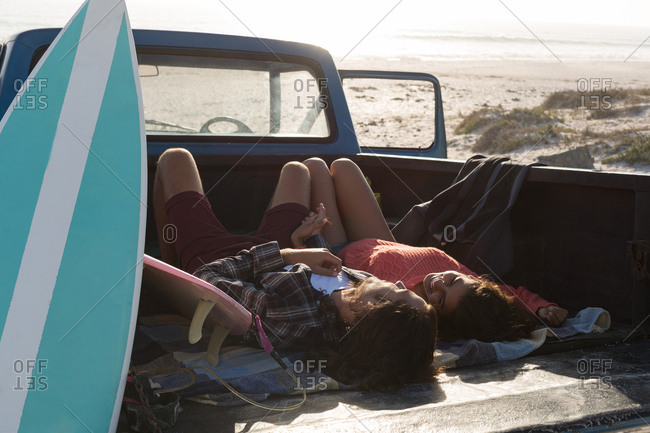 Couple relaxing in a pickup truck at beach on a sunny day
