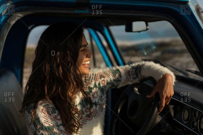 Happy woman sitting in a pickup truck