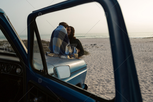 Couple romancing on a pickup truck bonnet in the beach