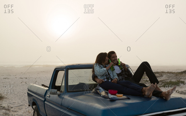 Couple having beer on a pickup truck bonnet in the beach