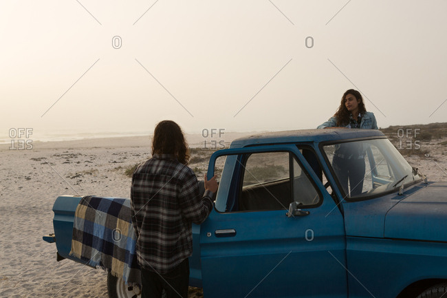 Couple standing with their pickup truck in the beach
