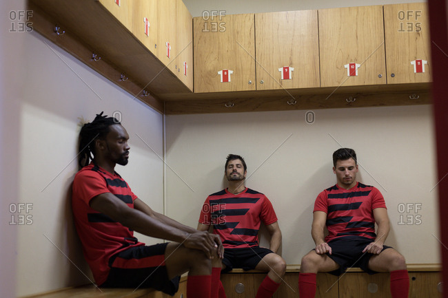 Football players relaxing on bench in dressing room