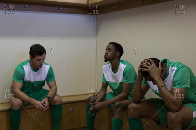 Tense football players sitting on dressing room